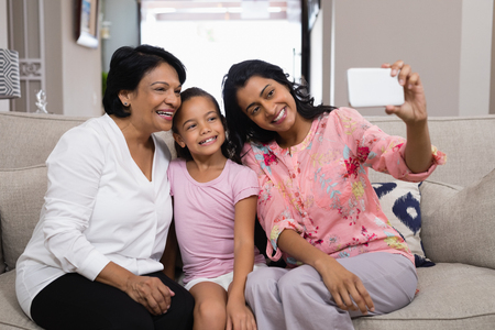 generation gap: Happy multi-generation family taking selfie while sitting together at home