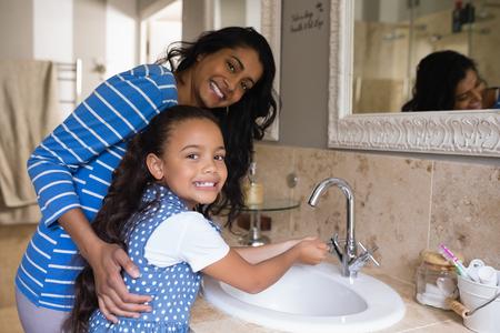 浴室の流しに母の手洗いと笑みを浮かべて少女の肖像画