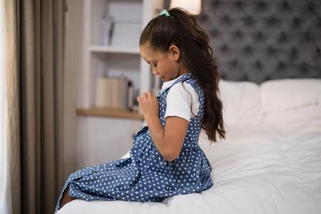 niños vistiendose: Vista lateral de la niña vestirse mientras está sentado en la cama en casa