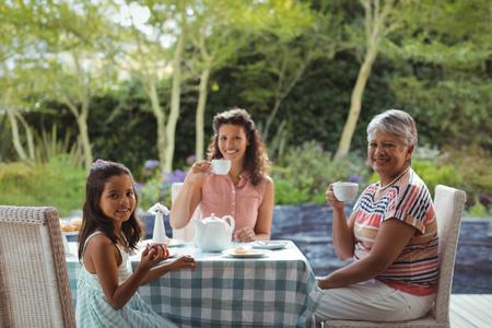 Portrait of happy family having tea at home