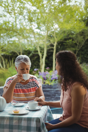 Mother and daughter having tea at home