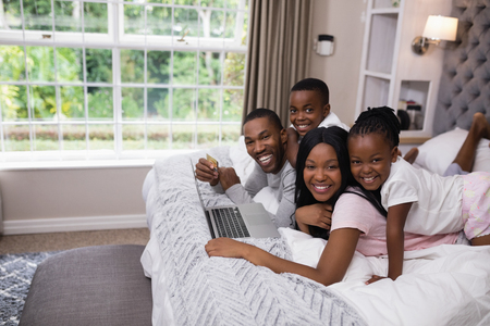 Portrait of smiling family shopping online while lying on bed at home Foto de archivo