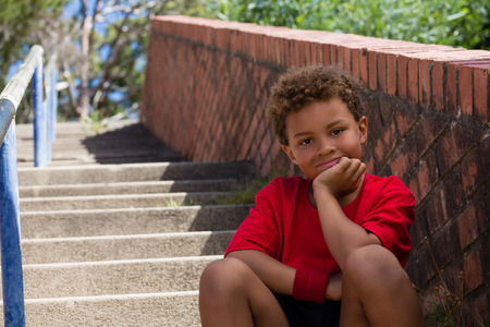 Portrait of boy sitting on staircase in the boot camp on a sunny day Stock Photo