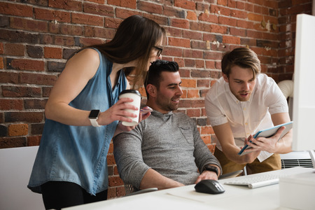 Executives discussing over digital tablet in office Stock Photo