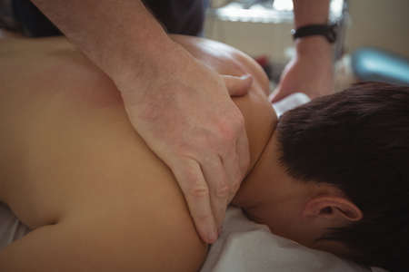 bodycare: Man receiving shoulder massage from therapist in spa LANG_EVOIMAGES