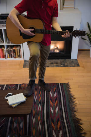 pastime: Man playing guitar in living room at home