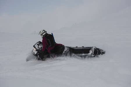 Man riding snowmobile in snowy alps during winter LANG_EVOIMAGES
