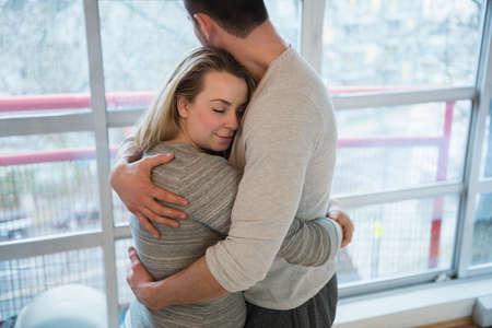 poblíž: Láskyplný pár se objímat navzájem v blízkosti okna doma