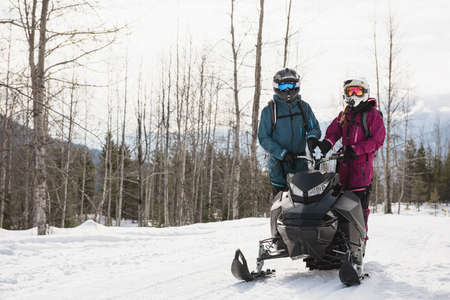 wintertime: Couple standing together on snowmobile in snowy alps during winter