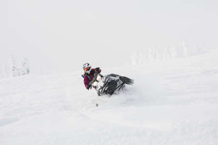 wintertime: Woman riding snowmobile in snowy alps during winter