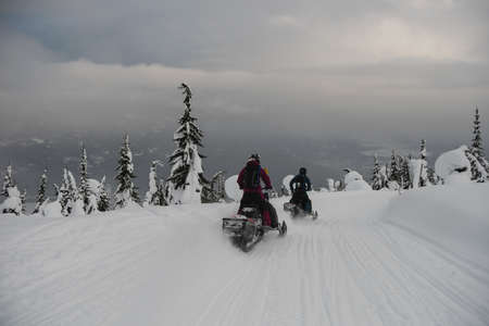 wintertime: Couple riding snowmobile in snowy alps during winter LANG_EVOIMAGES