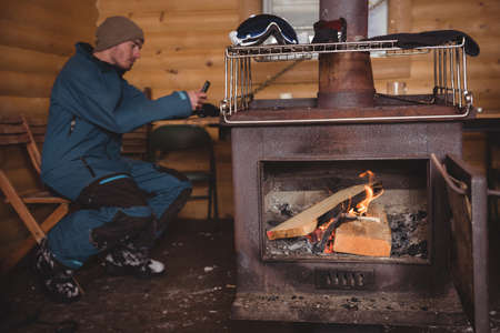 wintertime: Man using mobile phone near wood burning stove at log cabin
