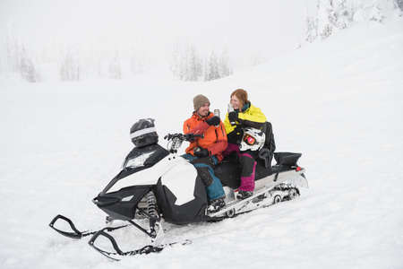 wintertime: Couple having coffee from thermos while relaxing on snowmobile during winter