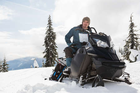 wintertime: Man holding a map while sitting on snowmobile in snowy alps during winter