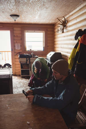 wintertime: Man using mobile phone in the log cabin