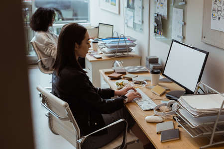 attentive: Female executive working on computer at desk in office
