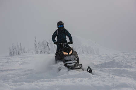 wintertime: Man riding snowmobile in snowy alps during winter LANG_EVOIMAGES