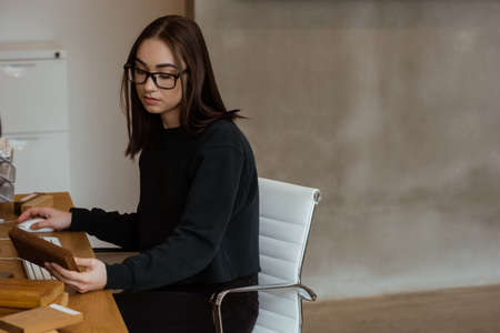 attentive: Female executive examining a wooden slab at desk in office