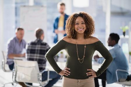 オフィスで腰に手を持つエグゼクティブ立っている女性の肖像画
