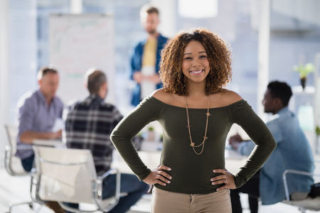 Portrait of female executive standing with hands on hip in the office Stok Fotoğraf - 81565888