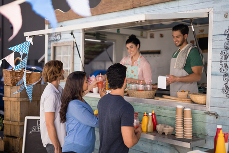 leaning on the truck: Smiling waiter taking order from customer at counter