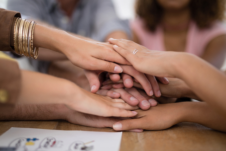 Executives forming hand stack on table in the office