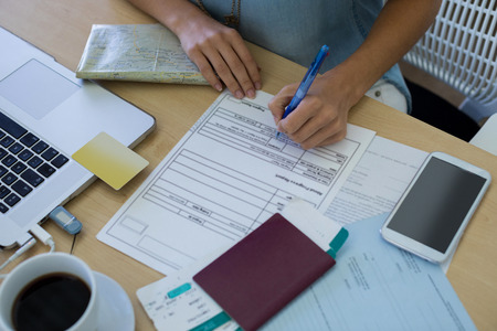Close-up of female executive filling form at her desk in office