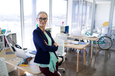 pen holder: Portrait of executive standing with arms crossed at her desk in office Stock Photo