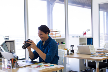 stylus pen: Male executive reviewing captured photograph at his desk in office Stock Photo