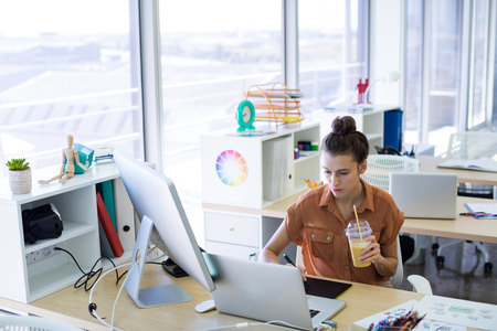 Female executive working over graphic tablet at her desk in office