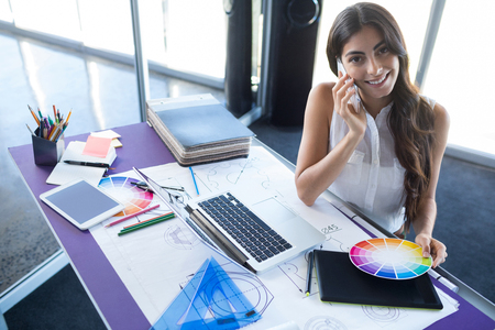 Female executive talking on mobile phone at her desk in office
