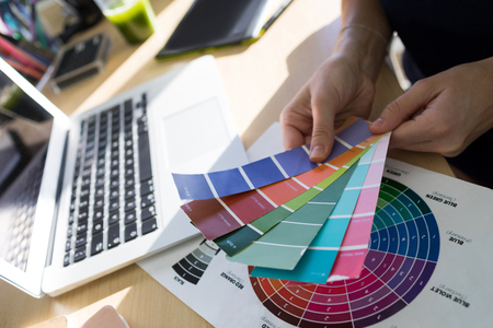 stylus: Close-up of female executives holding color shade swatch at her desk in office