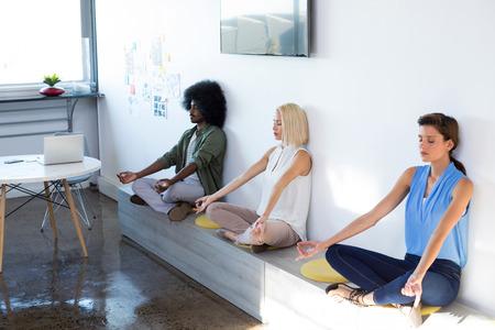 Dirigeants faisant du yoga au bureau Banque d'images - 81567592