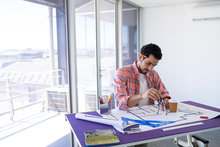 pen holder: Male architect working on blueprint over drafting table in office Stock Photo