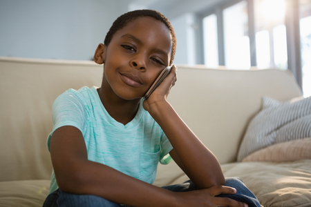Portrait of boy talking on mobile phone in the living room at home