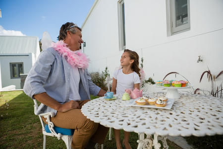 pretending: Father and daughter in fairy costume having fun in the backyard