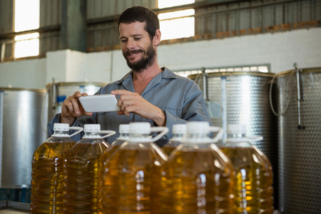 pone: Smiling working taking a photo of olive oil bottles in factory