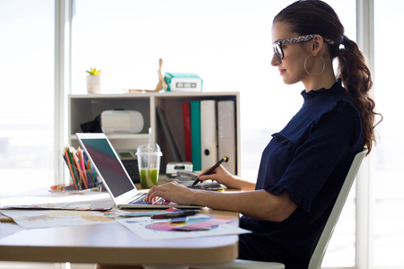stylus pen: Female executive working over laptop and graphic tablet at her desk in office Stock Photo