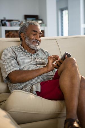 年配の男性が自宅のリビング ルームで携帯電話を使用して