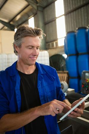 Smiling worker using digital tablet in factory