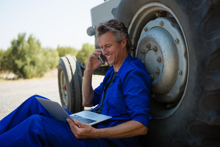 Worker talking on mobile phone while using laptop on a sunny day