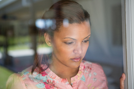 Thoughtful woman looking through window at home Banco de Imagens