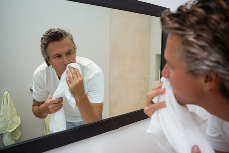 Man wiping his face with towel in bathroom Stock Photo - 81574435