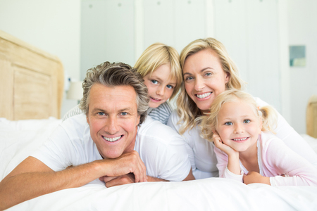 nightwear: Portrait of happy family lying together on bed in bedroom