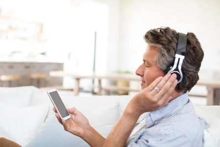 Man listening to music on headphones in living room