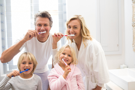 Family brushing teeth together in the bathroom at home Stock Photo