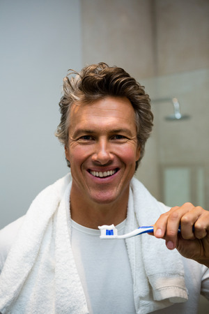 Portrait of man holding toothbrush with toothpaste in bathroom