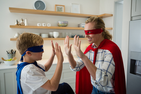 pretending: Mother and son pretending to be superhero in the kitchen at home Stock Photo