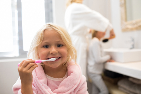 Portrait of girl brushing teeth in bathroom Stock Photo