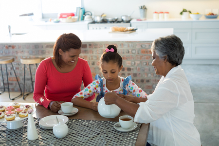 the grand daughter: Happy multi-generation family having tea in dining table at home